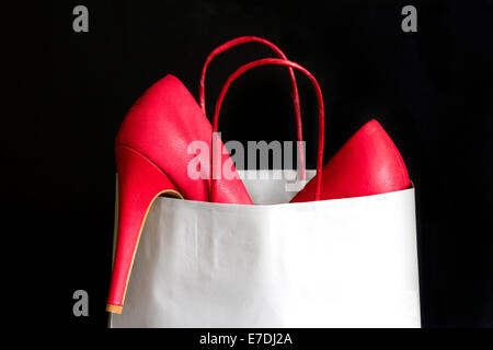 High heels red shoes in shopping bag against black - Stock Photo