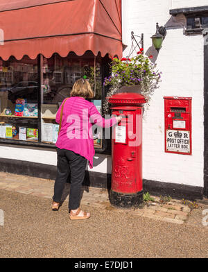 Woman posting a letter in an old fashioned post box in Woolpit Suffolk - Stock Photo