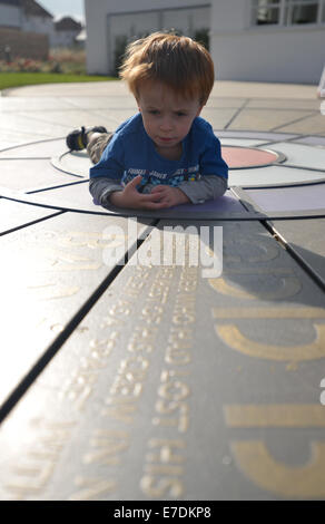 Young boy looking at the RAF memorial on the ground at the restored 1930s art deco WWII West Malling Airfield control - Stock Photo