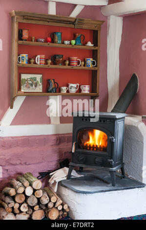 A cottage interior with a wood-burning stove installed in the sittingroom - Stock Photo