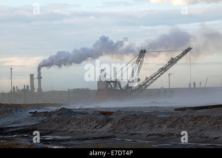 Industrial landscape with smoke stacks and mining dragline at Fort McMurray, Alberta, Canada - Stock Photo