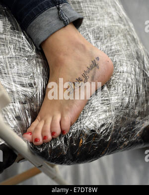 Garden City, New York, USA. 14th Sep, 2014. On her foot, a woman has just gotten a new tattoo of 'Love yourself' - Stock Photo