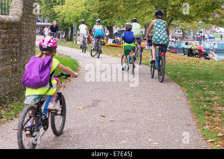 group of cyclists adults and children cycling riding bicycles together on a cycle path helping to cut congestion - Stock Photo