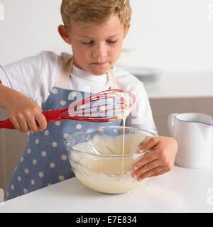 boy whisking batter to make pancakes - Stock Photo