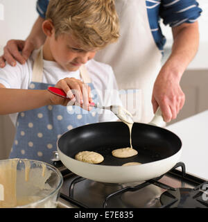 Pouring pancake batter in a frying pan - Stock Photo