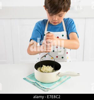 Boy mashing potatoes in a saucepan, 7 years - Stock Photo