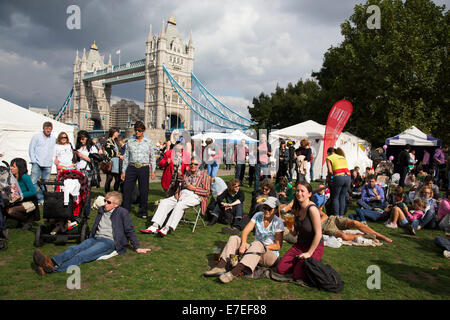 People gathering to hang out, listen to bands and other activities at the Blue Ribbon Village. Thames Festival London - Stock Photo
