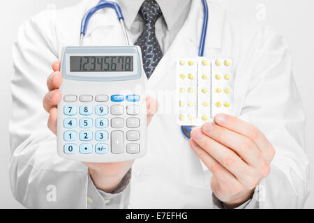 Doctor holdling calculator and pills in his hands - heath care concept - Stock Photo