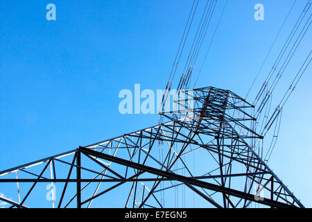 closeup under-view of towering steel pylon supporting electric power cables - Stock Photo