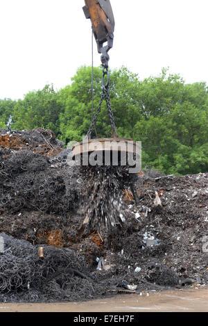 magnetic grab on crane lifting metal at scrapyard uk - Stock Photo