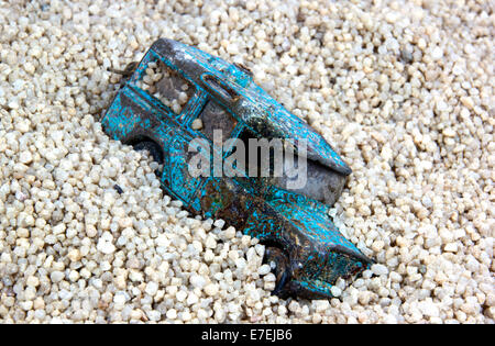 old battered blue toy car abandoned in sand pit - Stock Photo