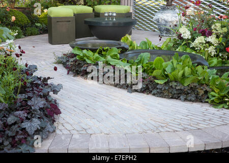 Garden - Bacchus Garden - view of garden with stone path leading to seating outdoor living area with water pool - Stock Photo