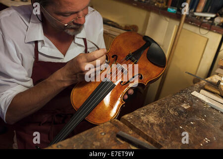 Violin maker in workshop in Rome - Stock Photo