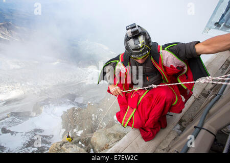Base jumpers wearing wing suites prepare to jump from the Aiguille Du midi above Chamonix, France, with tourists - Stock Photo