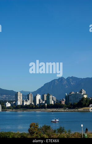A False Creek ferry on English Bay with West End high rises and North Shore mountains from Vanier Park, Vancouver, - Stock Photo