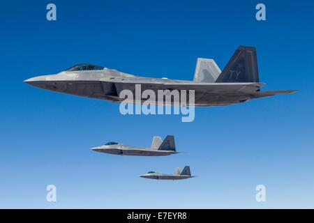Three U.S. Air Force F-22 Raptors cruise above Nevada. - Stock Photo