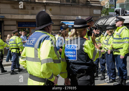 A police evidence gatherer uses a video camera to carry out overt surveillance on the pro Gaza protest. Manchester, - Stock Photo
