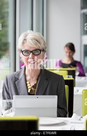 Caucasian businesswoman using tablet computer in restaurant