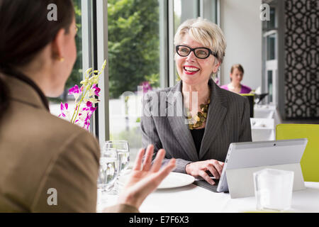 Caucasian businesswomen working in restaurant - Stock Photo