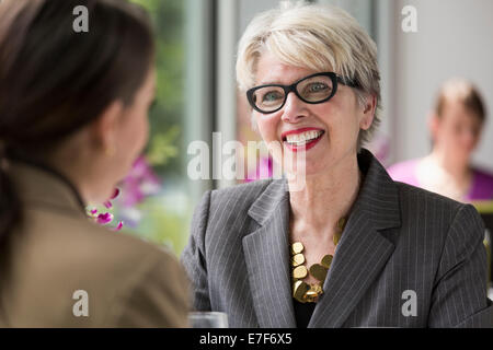 Caucasian businesswomen talking in restaurant - Stock Photo