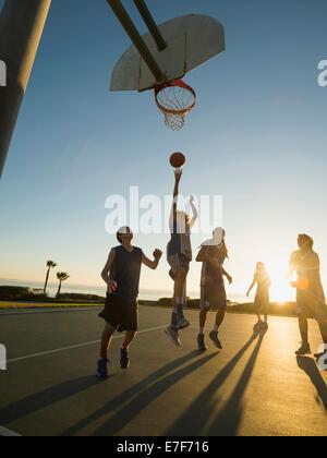 Back lit basketball teams playing on court - Stock Photo
