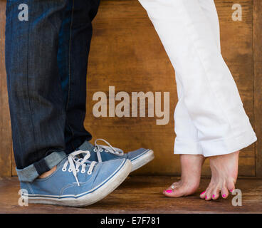 Woman standing on tiptoes to kiss boyfriend - Stock Photo