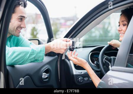 Man giving girlfriend keys to car - Stock Photo