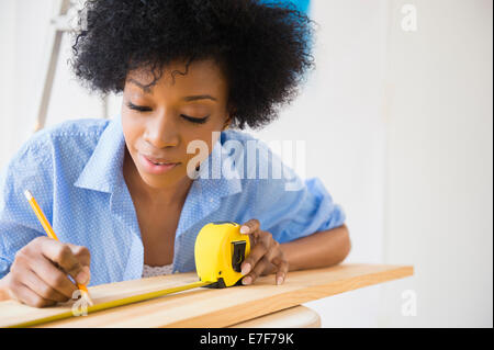 African American woman measuring wood