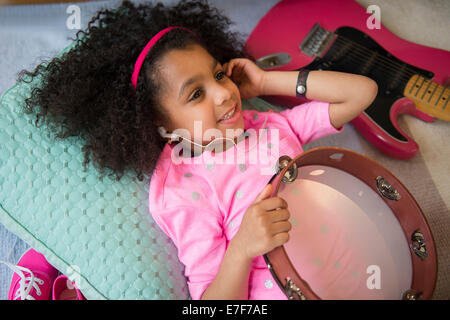 African American girl listening to music holding tambourine - Stock Photo