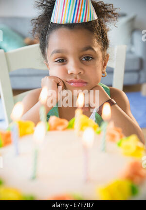 African American girl pouting at birthday cake