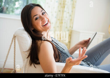 Woman using tablet computer in armchair - Stock Photo