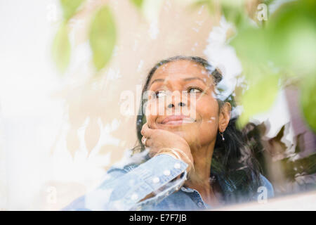 Mixed race woman looking out window - Stock Photo