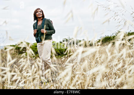 Black woman hiking on rural hillside - Stock Photo