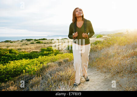 Black woman standing on rural hillside - Stock Photo