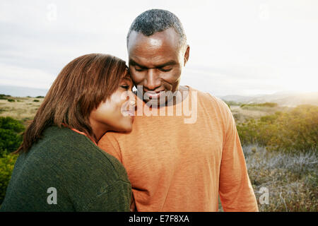 Black couple hugging on rural hillside - Stock Photo