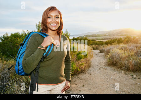 Black woman smiling on rural hillside - Stock Photo
