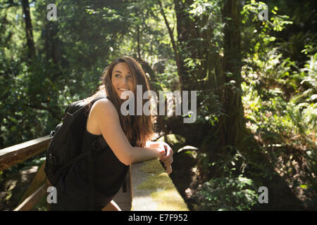 Caucasian woman standing on wooden bridge in forest - Stock Photo