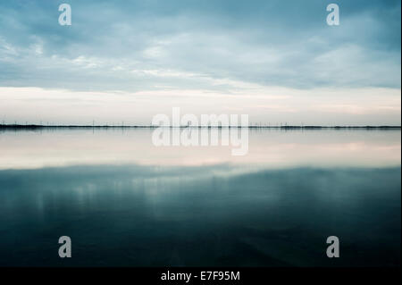 Clouds reflected in still rural lake - Stock Photo