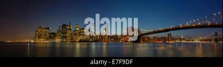 Panoramic view of New York city skyline illuminated at night, New York, United States - Stock Photo