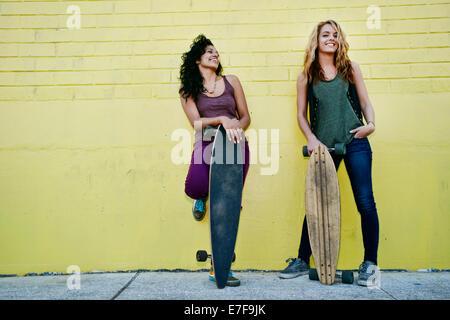 Women holding skateboards on city street - Stock Photo