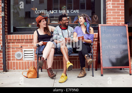 Friends sitting outside coffee shop on city street - Stock Photo