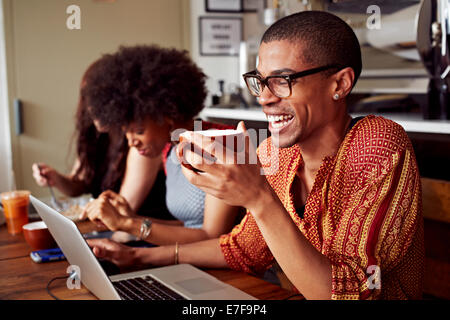 People using technology in coffee shop - Stock Photo