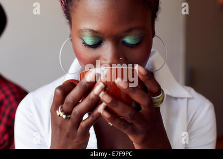 Woman drinking cup of coffee in cafe - Stock Photo