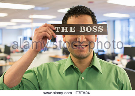 Hispanic businessman holding 'The Boss' sign over face - Stock Photo