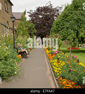 Colourful display of spring flowers beside lawns and trees with people relaxing on park bench in Bath Gardens, Bakewell - Stock Photo