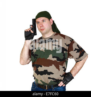 Thoughtful man in camouflage T-shirt and blue jeans with black handgun in hand. Isolated on white background - Stock Photo