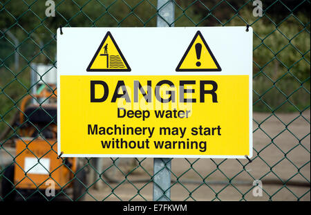 A warning sign attached to the wire mesh fence around water treatment works. - Stock Photo