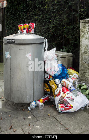 Overfull rubbish bin / garbage can with trash around and beer cans piled on top in city street - Stock Photo