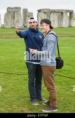 Stonehenge / Stone Henge with tourists / tourist taking a selfie photograph / photographs / self portrait picture - Stock Photo