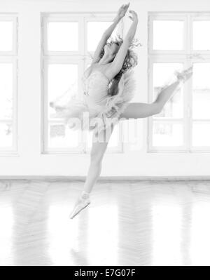 Young, beautifull ballerina exercising in studio. A black and white image with grain added as effect. - Stock Photo